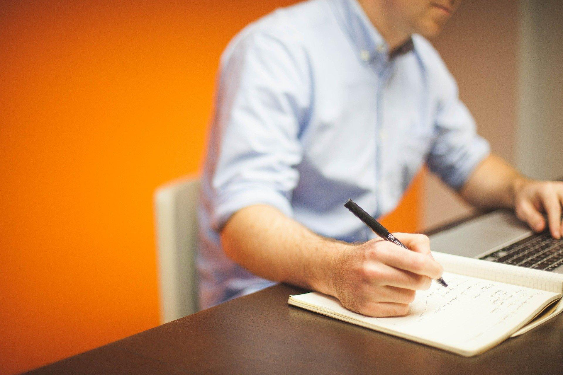 Mann lektoriert Text und macht Notizen