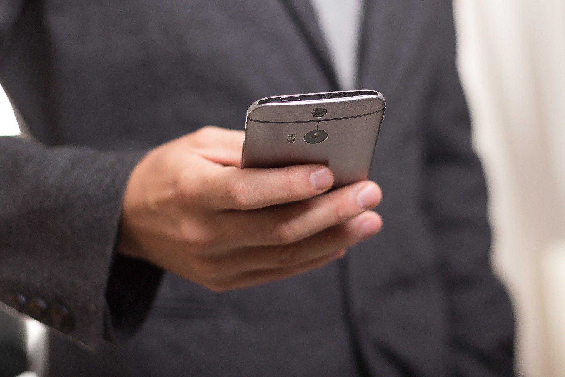 Mann nimmt mit Smartphone Kontakt auf